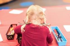 Enfant avec les tresses blondes colorant à une table d'art Photo libre de droits