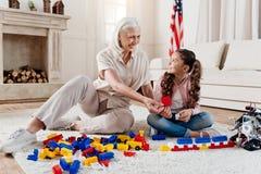 Enfant avec plaisir positif jouant avec sa grand-mère Photos stock