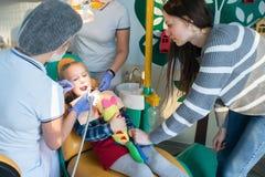 Enfant avec sa mère dans le bureau de dentiste Images libres de droits