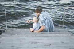 Enfant avec son père s'asseyant sur le pilier Image libre de droits