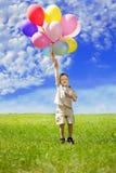 Enfant avec un groupe de ballons dans des leurs mains Photos libres de droits