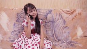 Enfant avec un mobile Petite fille dans une belle robe avec un téléphone portable Fille dans une robe avec des coeurs banque de vidéos