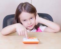 Enfant avec une calculatrice Photographie stock