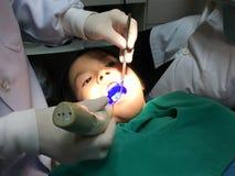 Enfant ayant le contrôle de bouche dans la clinique dentaire images libres de droits