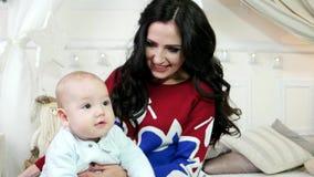 Enfant, bébé dans les bras de sa mère, mère jouant avec son petit fils, l'amusement de famille jouant pendant l'hiver clips vidéos
