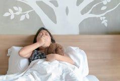 Enfant baîllant sur le lit dans le matin photographie stock