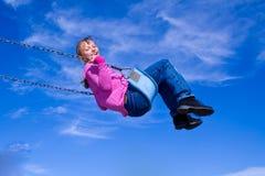 Enfant balançant dans le ciel. Photo libre de droits