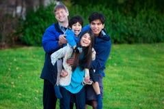 Enfant biracial handicapé montant sur le dos sur sa soeur, famille photos stock