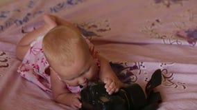 Enfant blond dans la robe se trouvant sur le lit banque de vidéos