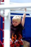 Enfant blond de garçon sur des bars Photos libres de droits