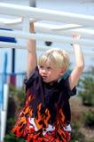 Enfant blond de garçon sur des bars Image libre de droits