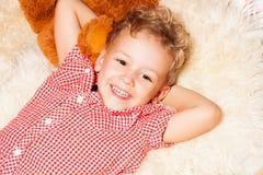Enfant blond heureux sur les fourrures Photo stock