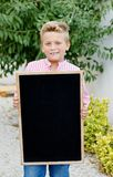 Enfant blond tenant une ardoise photographie stock libre de droits