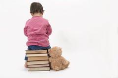 Enfant bouleversé s'asseyant sur des livres avec elle teddybear Images stock