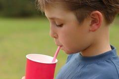 Enfant buvant par une paille photo libre de droits