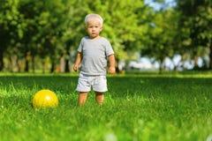 Enfant calme jouant avec la boule dehors images stock