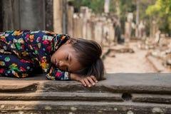 Enfant cambodgien de Khmer traditionnel non identifié se reposant au-dessus des ruines de temple. Photos libres de droits