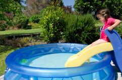 Enfant chez la piscine gonflable des enfants Image stock