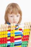 Enfant comptant sur l'abaque en bois coloré Image libre de droits