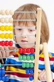 Enfant comptant sur l'abaque en bois coloré Images stock