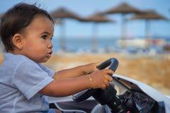 Enfant conduisant la voiture par la plage Photo libre de droits