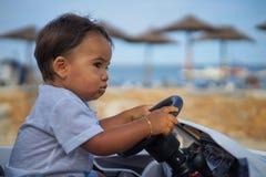 Enfant conduisant la voiture par la plage Photographie stock libre de droits