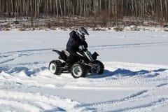 Enfant conduisant un quadruple dans la neige Image stock