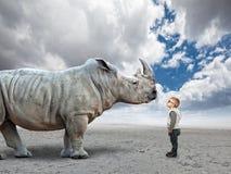 Enfant contre le rhinocéros images libres de droits