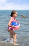 Enfant courant avec une boule colorée Photos stock
