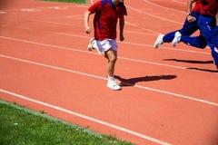 Enfant courant sur la voie dans le stade Photos stock