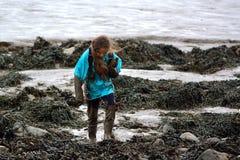 Enfant couvert dans la boue sur le bord de la mer Image libre de droits