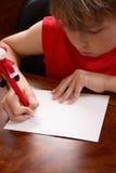 Enfant écrivant une lettre Images libres de droits