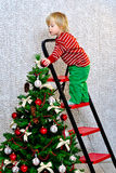 Enfant décorant l'arbre de Noël Image libre de droits