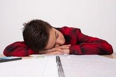 Enfant déprimé sur la table dans la classe, avec des fournitures scolaires sur la table photographie stock