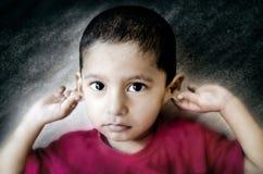 enfant désolé tenant des oreilles Photo stock