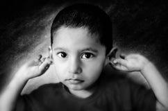 enfant désolé tenant le portrait de monochrome d'oreilles Images libres de droits