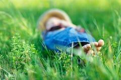 Enfant détendant dans l'herbe sur le champ Foyer à pied photo libre de droits
