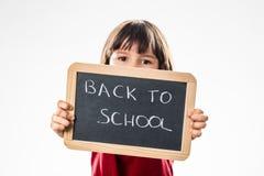 Enfant déterminé avertissant environ de nouveau à l'école sur l'ardoise d'écriture Photos stock