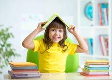 Enfant d'étudiant avec un livre au-dessus de sa tête Images stock