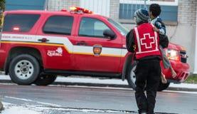 Enfant d'aide de volontaire de Croix-Rouge après bouche d'incendie photo libre de droits