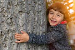 Enfant d'enfant embrassant la nature extérieure de protection de l'environnement d'arbre Photos stock