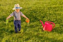 Enfant d'enfant en bas âge dehors Un chapeau de paille de port de bébé garçon an utilisant la boîte d'arrosage photographie stock libre de droits