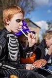 Enfant d'une chevelure rouge avec le costume squelettique mangeant la sucrerie colorée Veille de la toussaint Photos libres de droits