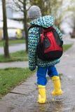Enfant dans des bottes de pluie marchant dans le magma Images stock