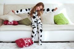 Enfant dans des pyjamas d'impression de vache Images libres de droits