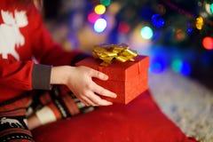 Enfant dans des pyjamas tenant un cadeau par un arbre de Noël le réveillon de Noël Photographie stock