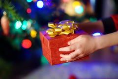 Enfant dans des pyjamas tenant un cadeau par un arbre de Noël le réveillon de Noël Photographie stock libre de droits