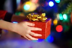 Enfant dans des pyjamas tenant un cadeau par un arbre de Noël le réveillon de Noël Image stock