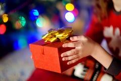 Enfant dans des pyjamas tenant un cadeau par un arbre de Noël le réveillon de Noël Photo libre de droits