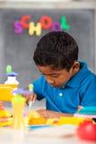 Enfant dans l'arrangement à la maison d'école Image libre de droits